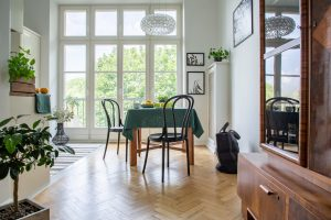 Real photo of a table with green cloth, chairs and close-up of a cupboard in a retro dining room interior